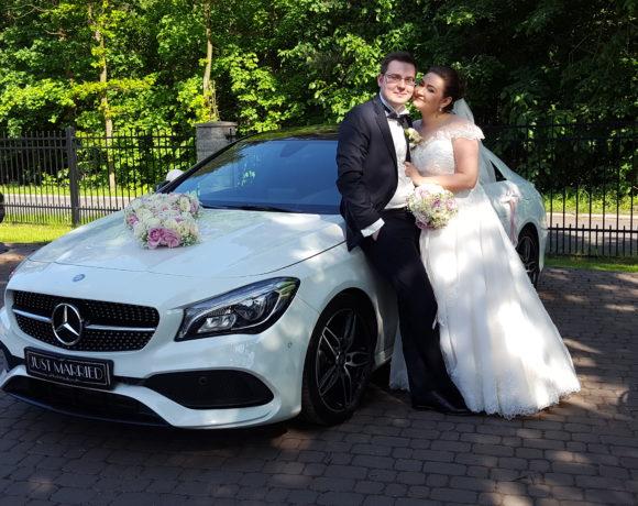 Szczęśliwi nowożeńcy przy limuzynie