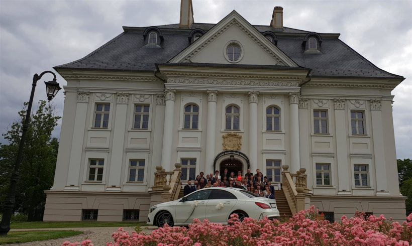 Auto do ślubu przed pięknym pałacem