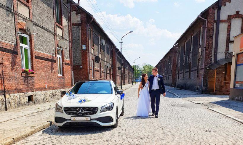 Szybki spacer nowych małżonków w towarzystwie Mercedesa